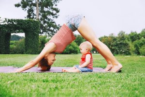 Young woman doing yoga with baby in the summer park. Beautiful mother and daughter like a little buddha exercising on green grass on nature. Family outdoors. Parent with child spend time together. – ©Adobe